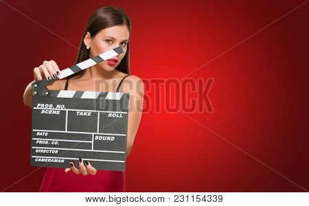 Woman In A Red Dress Holding Clapper Board against a red background