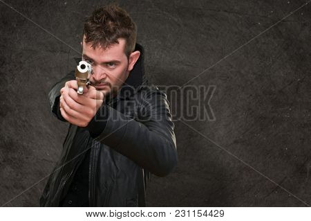 young man pointing with gun against a grunge background
