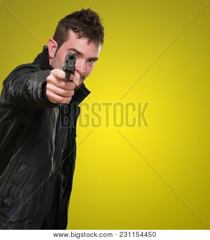 man with leather jacket pointing with gun against a yellow background