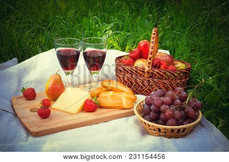 Outdoor Picnic Setting With Two Glasses Of Red Wine, Cheese And Ripe Fruits On Napkin