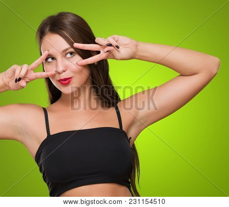Young Woman Peeking Through Fingers against a green background