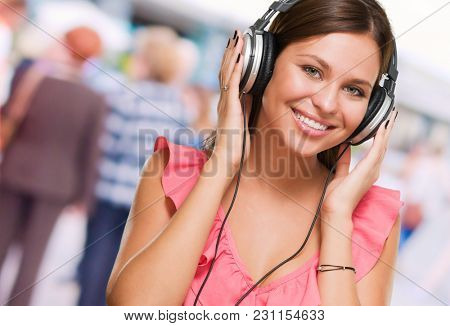 Beautiful Young Woman Wearing Headphones against a street background