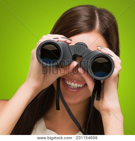 Portrait Of A Young Woman Holding Binoculars against a green background