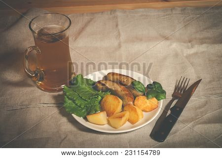 Mug Of Beer With Plate Of Grilled Sausages And Roasted Potato On Table