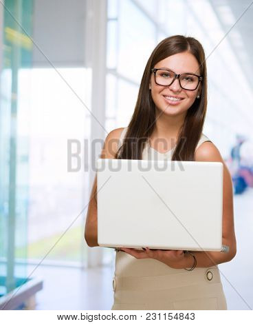 Happy Young Woman Holding Laptop against an abstract background