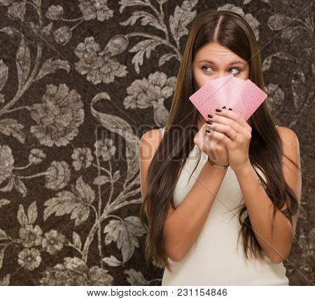 Pretty Young Woman Holding Playing Cards against a vintage background