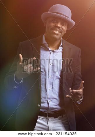 Image of handsome african man wearing hat posing in studio.