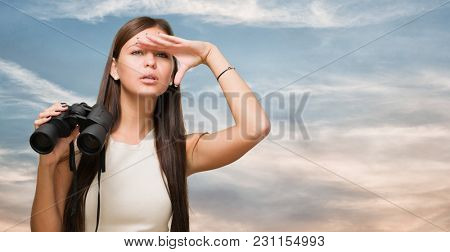 Portrait Of A Young Woman Holding Binoculars And Searching, outdoor