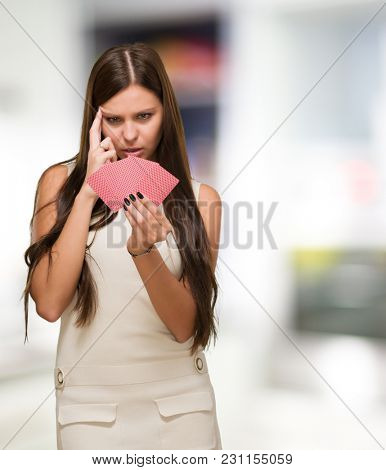 Confused Young Woman Holding Playing Cards against an abstract background