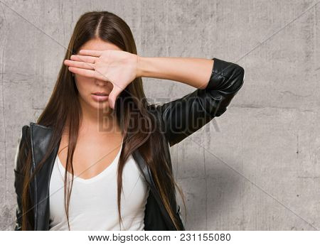 Portrait of a Woman Covering Her Eyes against a grunge background