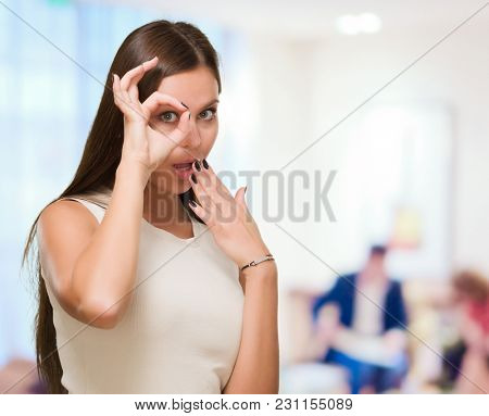 Surprised Young Woman Looking Through Imaginary Binocular against an abstract background