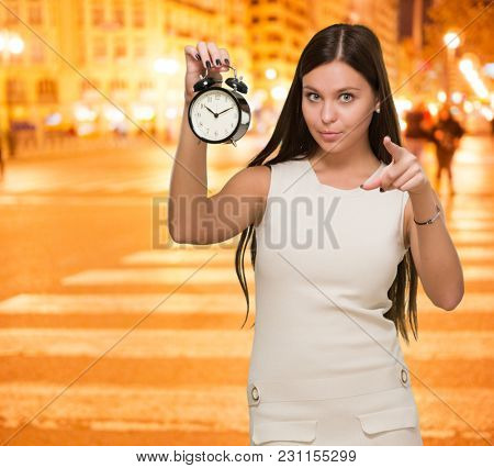 Woman Holding Alarm Clock and pointing, outdoor