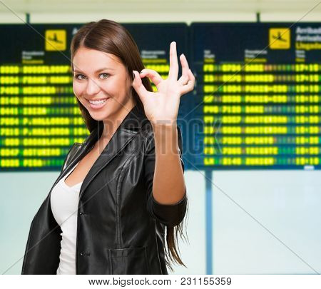 Portrait Of Cheerful Young Woman Gesturing Okay Sign at the airport