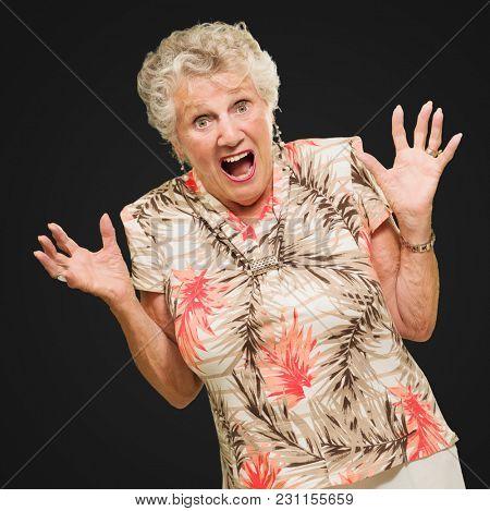 Portrait Of Shocked Senior Woman On Black Background