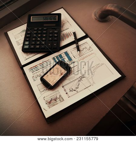 Folder With The Charts Of Financial Analysis. Diagrams In The Phone's Screen, Next Is Calculator And