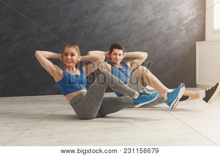 Fitness Couple Doing Crunches Indoors. Young Sporty Man And Woman Making Sits-up On Mat. Healthy Lif