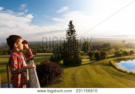 Boy Looks At The Mountains Through Binoculars. Child Standing By The Wooden Railing And Holding Bino