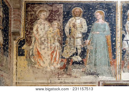 VERONA, ITALY - MAY 27: Enthroned Madonna and Child, Saints George, Catherine and a worshipper Knight, fresco in the church of San Pietro Martire in Verona, Italy, on May 27, 2017.