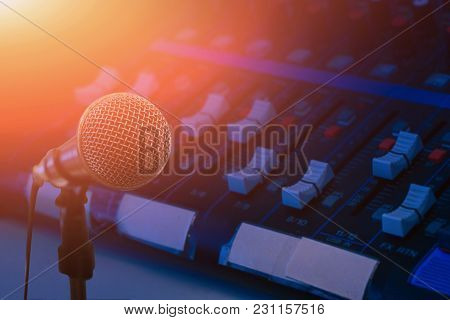 Microphone Over The Abstract Blurred Photo Of Conference Hall Or Seminar Room Background, Dark Backg