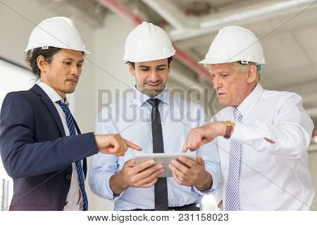 Two Middle Aged Men In Formalwear And Hard Hat Showing Something To Smiling Partner On Tablet. Two A