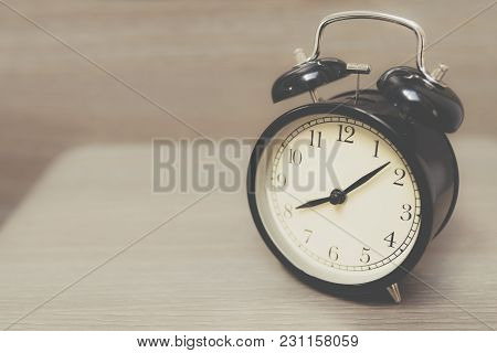 Retro Alarm Clock On Table With Vintage Background