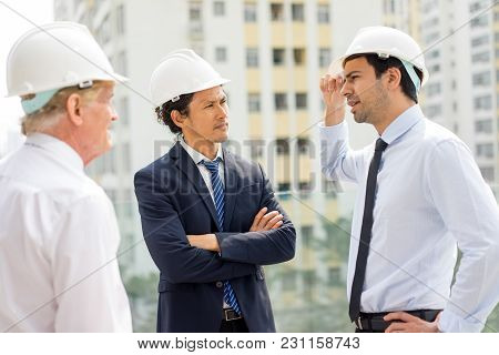 Young Engineer And His Colleague Explaining Something To Strict Man In Suit. Building Owner Visiting