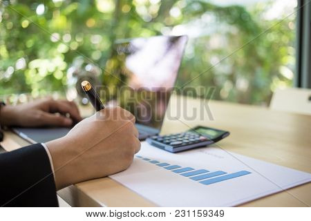 Close Up Shot Of A Businessman Writing On Charts Paper At Workstation. Modern Business Man Writing O
