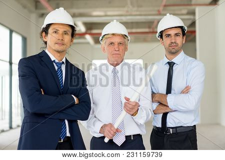 Portrait Of Three Serious Men In Formalwear And Hard Hats With Blueprint On Site Area. Team Of Engin