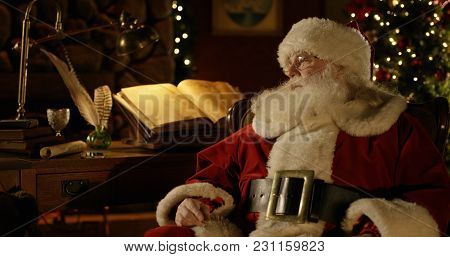 Santa Claus Rests At His Work Bench In A Room Filled With Christmas Decorations.