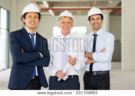 Portrait Of Three Smiling Men In Formalwear And Hard Hats With Blueprint At Site. Team Of Building C