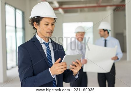 Man In Formalwear And Helmet Using Tablet, His Two Partners Reviewing Blueprint In Blurred Backgroun