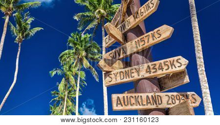 Street sign on the beach indicating directions to different places of the world, taken at Samoa