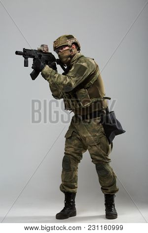 Full-length photo of soldier in camouflage with gun