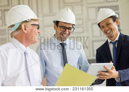 Three Happy Men In Hardhat And Ties Looking At Tablet Screen And Laughing. Group Of Construction Man