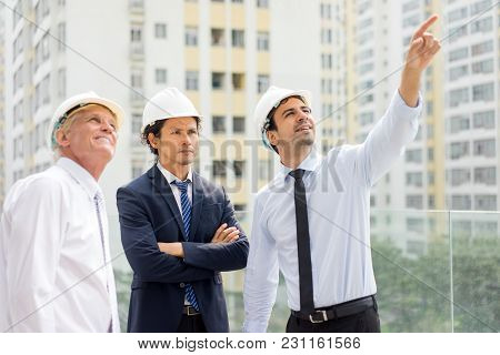 Young Engineer Pointing At Something Up To His Colleague And Serious Man In Suit With Folded Arms. P
