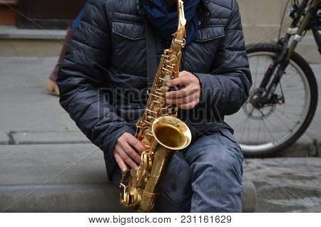A Street Musician Is Playing For Money