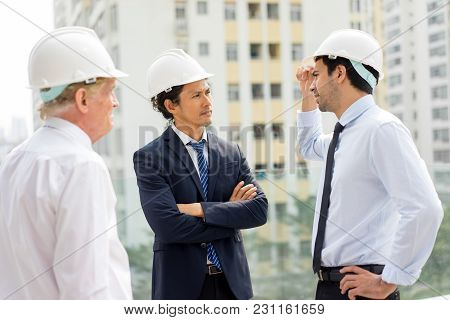 Strict Man In Helmet And Suit With Folded Arms Listening To Two Technical Experts. Two Engineers Rep