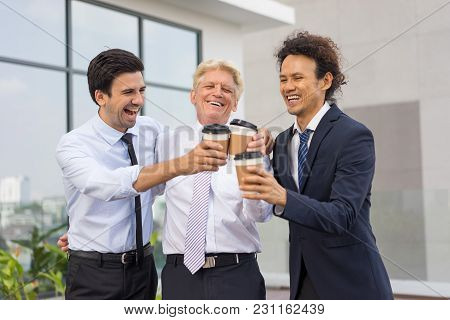 Closeup Of Business Team Of Three Cheerful Diverse People Embracing, Clinking Disposable Cups And St