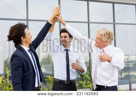 Closeup Of Business Team Of Three Smiling Diverse People High Fiving, Showing Thumbs Up And Standing