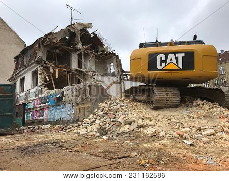 Copenhagen, Denmark - March 14, 2018: Demolition Of An Old House With Yellow Cat Excavator Power Sho
