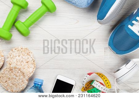Fitness concept background with sneakers, dumbbells, water bottle, towel and headphones. Top view with space for your text