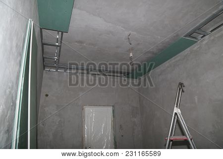 Fixing Plaster Boards At The Ceiling Of A House Under Construction.