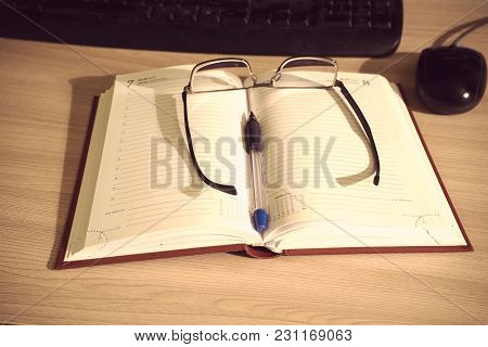 Glasses And Pen On An Open Book For Entries On The Table Next To The Keyboard And Mouse
