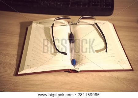 Glasses And Pen On An Open Book For Entries On The Table Next To The Keyboard