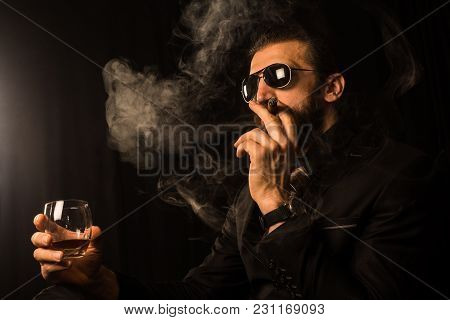 The Elegant Mafia Boss Or Gentleman In Black Suit Is Smoking Cigar And Holding Alcohol Drink In Hand