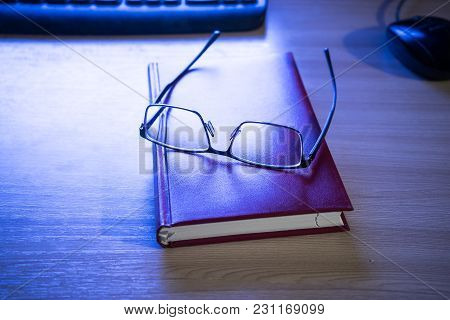 Book And Glasses On The Table Next To The Keyboard And Mouse Lighted By A Monitor
