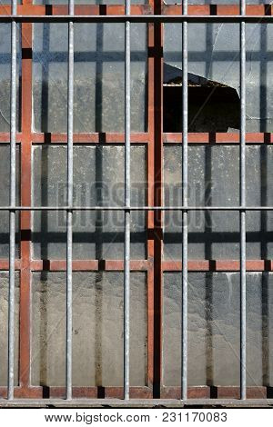 A Broken Window Of An Abandoned Industrial Building With Barred Window..