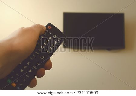 Tv Remote Control In Male Hand In Front Of Widescreen Tv Set With Blank Screen On Yellow Wall Backgr