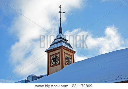 Tower Of The Church With A Clock And A Windy Banner.