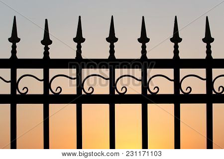 Metal Fence At Sunset . In The Park In Nature